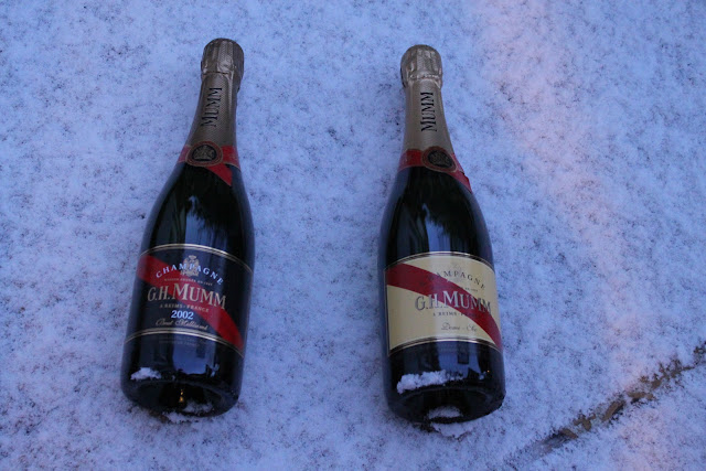 Mumm champagne being kept cold on a snowy balcony.