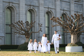 Family with 4 girls and 1 boy modeling outside of a church