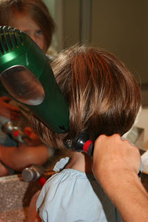 Side view of young girl's hair being styled with a blow dryer and round brush