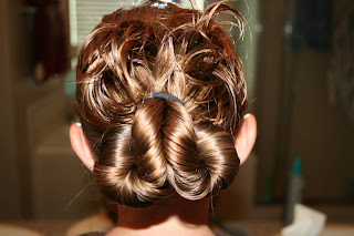 """Young girl's hair being styled into """"Pretzel-Twist Messy Bun"""""""