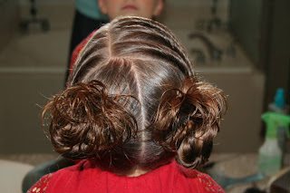 "Back view of young girl's hair styled into ""Triple Twists and Messy Buns"""