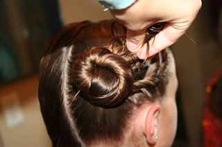"Young girl's hair being styled into ""Triple Twists and Messy Buns"""