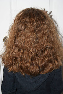 Back view of Young girl' modeling 2nd Day Curls from Double-French Braids
