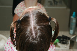 """Back view of young girl's hair being styled into """"Two Messy Twists on Top"""" Hairstyle"""