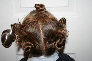 "Back view of young girl modeling ""Holiday Twisty Buns"" hairstyle"