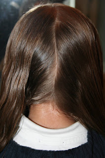 """Back view of young girl's hair being styled into """"Y"""" braid hairstyle"""