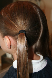 "Side view of young girl's hair being styled into ""Y"" braid hairstyle"
