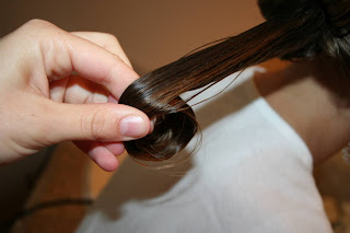 "Close up view of young girl's hair being styled into ""Teen Hair Bun"" hairstyle"