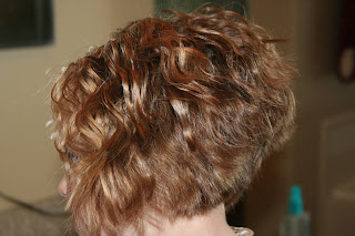 side view of young girl modeling 3-barrel curl hairstyle on her a-line bob