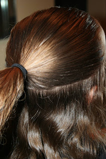"Side view of young girl's hair being styled into ""Flip Braided Heart"" hairstyle"