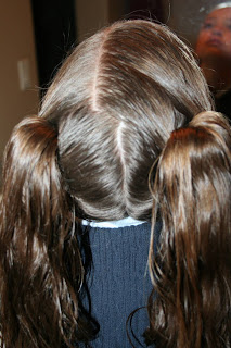 """Back view of a young girl's hair being styled into """"Two Hearts Twist"""" hairstyle"""