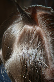 "Close up view of a young girl's hair being styled into ""French Designer Heart"" hairstyle"