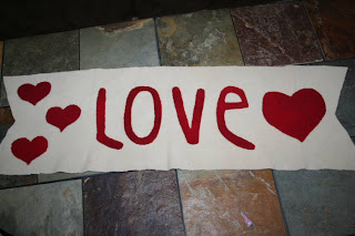 """Large white banner with the word """"love"""" on it surrounded by hearts"""