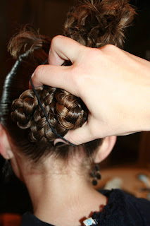 "Back view of young girl's hair being styled into ""bundled braids"" hairstyle"