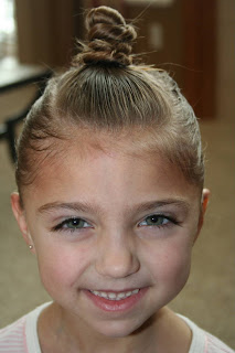 """Portrait view of young girl modeling """"The Bun-Hawk"""" hairstyle"""
