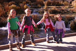 4 young sibling girls holding hands for a picture at a park by a lake
