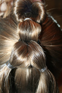 "Back view of young girl's hair being styled into ""Three-Leaf Clover Twists"" hairstyle"