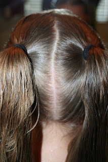 "Back view of young girl's hair being styled into ""Two-Leaf Clover"" hairstyle"