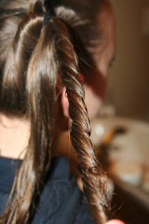 "Side view of young girl's hair being styled into ""Two-Leaf Clover"" hairstyle"