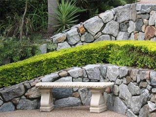 zid de sprijin, gradina mica, teren abrupt, piatra naturala, buxus, gard viu, banca piatra