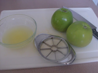 Cutting board with two apples, knife, apple corer and pineapple juice in a bowl for make ahead lunch prep.