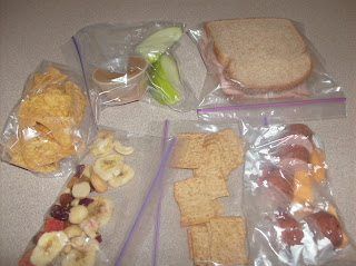 Overhead shot of ham n cheese sandwich, baggies with dried fruit, doritos and sausage and cheese slices for a week of make ahead lunch plan.