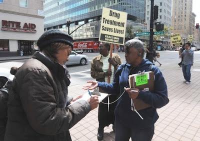 Gathering signatures for drug treatment programs. Three women on street corner.