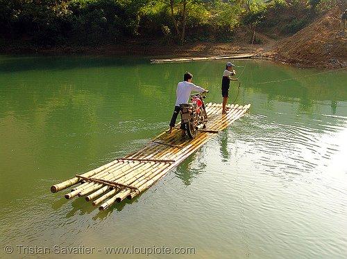 Moto atravezando rio em embarcação de bambu