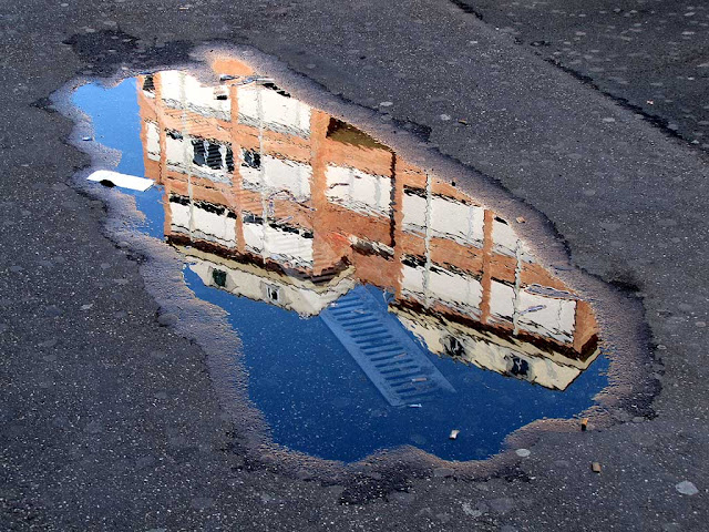 Building reflected in a pool of water, piazza Attias, Livorno