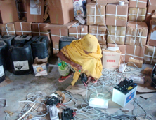 An engineer takes stalk of her equipment including light bulb and battery powered by solar energy.