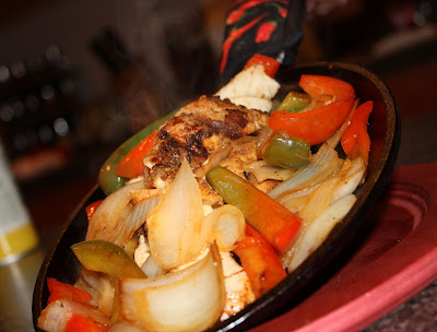 skillet with chicken, bell peppers, and onions