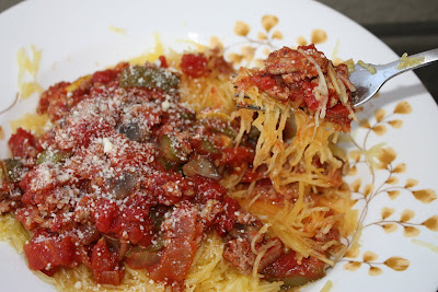 bowl of spaghetti squash covered in turkey vegetable ragu with a fork taking some from the dish