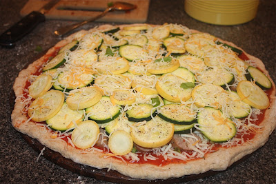 uncooked pizza dough topped with tomato sauce, cheese, sausage, zucchini, and squash