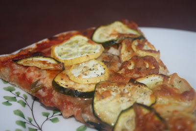 plate of pizza sliced topped with squash and zucchini
