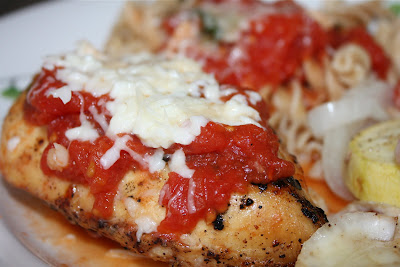 close up of piece of chicken topped with tomato sauce and cheese