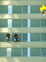 Lavadores de vidrios de ventanas en altura.Edificio de departamentos.