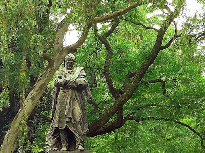 Estatua del prócer cabizbajo con los brazos cruzados