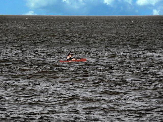 Hombre navegando en piragua en pleno mar.