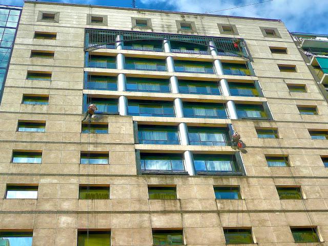 Trabajo en altura, dos operarios limpiando ventanas