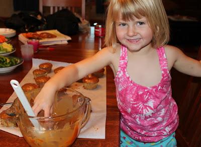 Little blonde girl dipping apple in caramel