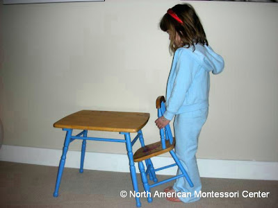 importance NAMC montessori practical life activities classroom girl pushing in chair