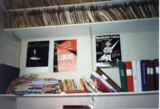 Ovanför en stökig och överfull vägghylla med böcker och pärmar sitter musikalposters, två för musikalen Lukas och en för musikalen Motljus.
