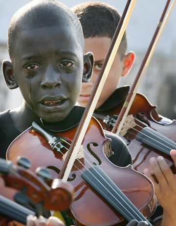 A boy cries as he plays violin at the funeral of his mentor, who helped him escape poverty