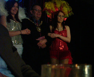 Belfast Lord Mayor Tom Hartley along about to be escorted on stage by two dancing girls at the launch of the tenth Cathedral Quarter Arts Festival