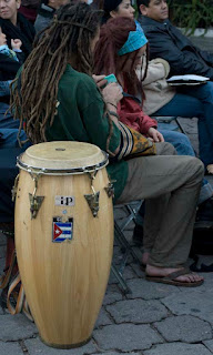 pareja areglándose las rastas a un lado de unos tambores