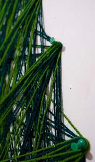 detalle de árbol de navidad hecho con estambre y tachuelas