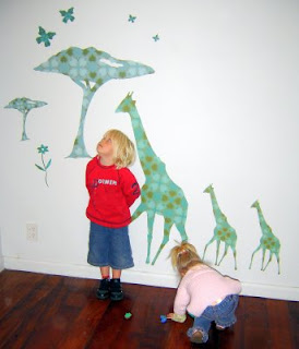 Two young children with giraffes wall decal