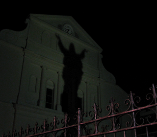 shadow of jesus statue reflected on st louis cathedral in new orleans