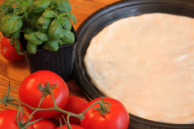 this is an Italian homemade pizza dough rising in a round cookie sheet style pizza pan with basil and tomatoes on a wooden oak table. This recipe is how to make homemade pizza dough  to be used in pizza rolls, pizza, rolls, pizza fritta, margarita pizza, garlic pizza and garlic knots