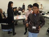 小学生の男の子が真似して歩くのにつかまって、歩き方をみています